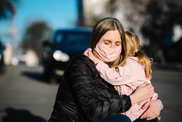 コロナウイルス。ママは赤ちゃんを抱擁し、さよならを言います。防護マスクの女性が路上で娘を受け入れる
