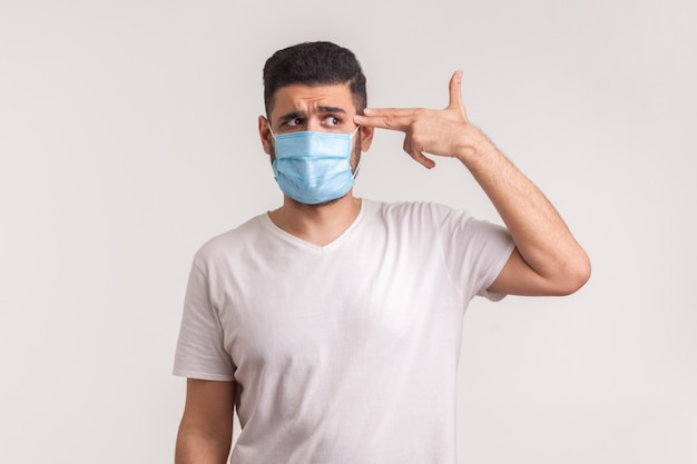 コロナウイルスによる死亡率。感染を恐れて、鉄砲のジェスチャーを頭に向けるマスクの絶望的な男