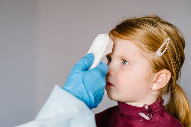 Coronavirus. nurse, doctor checks girl's body temperature using infrared forehead thermometer (gun) for virus symptom - epidemic outbreak concept. high temperature.