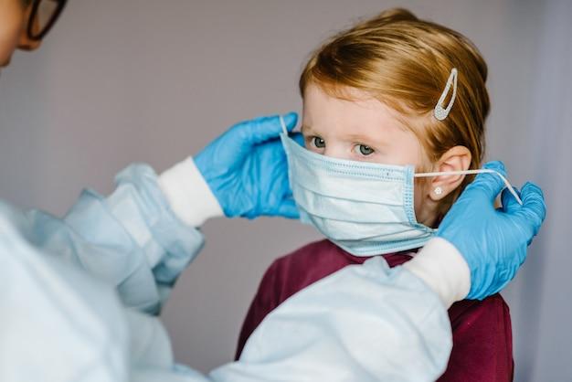 コロナウイルス。看護師、防護服の医者、子供のための顔に医療マスクを着用します。 covid-19感染に対する予防策。インフルエンザ、コロナウイルスの流行に対する保護の概念。