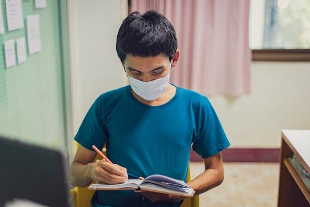 コロナウイルスまたはcovid-19。マスク保護を身に着けているアジア人の男性は家で働きます。