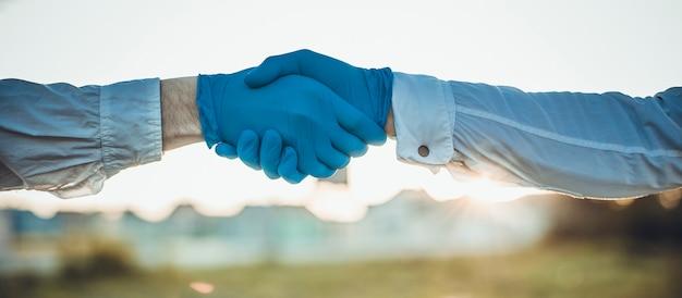 コロナウイルスまたはcovid-19細菌は、ハンドシェイクまたはタッチの概念によって広がります。握手にはノーと言ってください。ビジネスマンハンドシェイクとウイルスが広がります。黒い手袋を着用して同僚として一緒に手を繋いでいる医師。