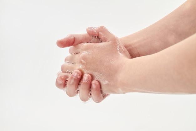 コロナウイルスまたはコビッド-19のコンセプト。石鹸で手を洗う小さな女の子。白い背景の上の石鹸で手を洗うのプロセス。クローズアップ、セレクティブフォーカス