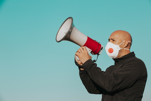 Coronavirus outbreak, angry man with medical face mask screaming into the megaphone, coronavirus, covid-2019 protest, economic crisis, worldwide pandemic