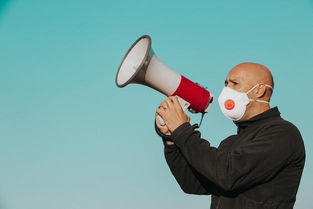 コロナウイルスの発生、メガフォンに向かって叫ぶ医療用フェイスマスクを持った怒っている男、コロナウイルス、covid-2019抗議、経済危機、世界的大流行