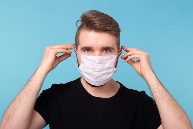 コロナウイルスの発生コビッドとパンデミックの概念。医療用使い捨てマスクを着用する男性