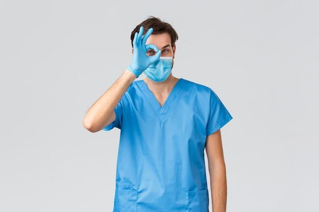 コロナウイルスの発生、病気と戦う医療従事者、病院のコンセプト。医療用マスク、スクラブ、手袋を着用したハンサムな医師が大丈夫な兆候を示し、erクリニックで患者の子供と遊んで、人々の命を救う
