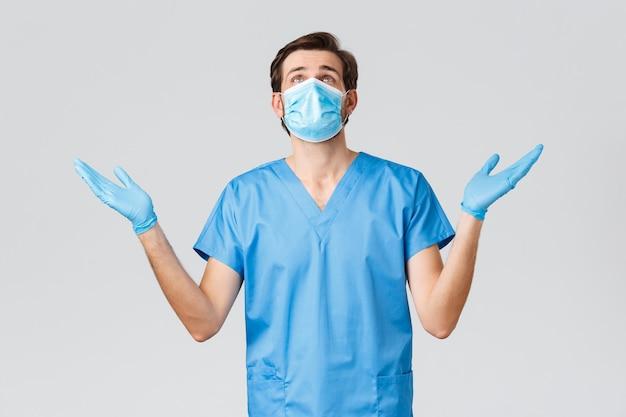 コロナウイルスの発生、病気と戦う医療従事者、病院のコンセプト。医療用マスクと青いマスクの希望に満ちた絶望的な医師、神の助けを求め、covid19で助けを祈ったり懇願したりする