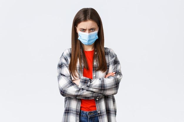 코로나바이러스 발병, 격리 여가, 사회적 거리 및 감정 개념. 의료용 마스크와 체크 캐주얼 셔츠를 입은 화난 젊은 여자 친구, 기분이 상하고, 으스스하고, 방어적으로 서 있다