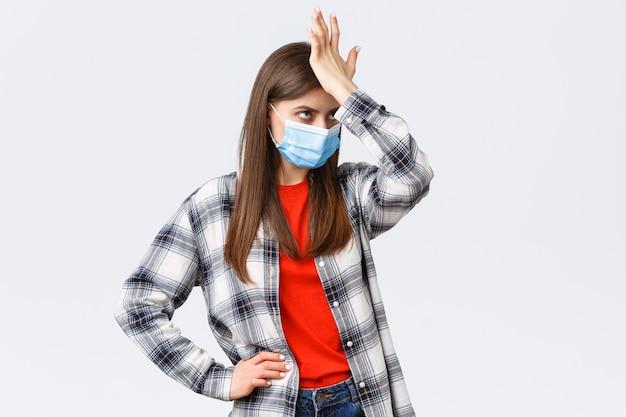 Вспышка коронавируса, досуг на карантине, социальное дистанцирование и концепция эмоций. обеспокоенная и раздраженная молодая женщина в медицинской маске бьет кулаком по лбу и закатывает глаза от чего-то глупого.