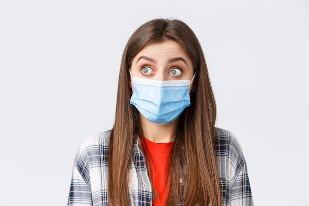コロナウイルスの発生、検疫の余暇、社会的距離と感情の概念。カジュアルな服装と医療用マスクを身に着けた驚いた白人女性のクローズアップ。