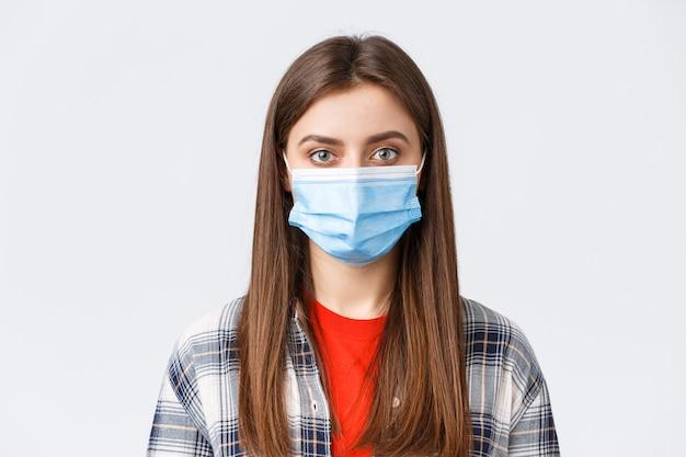 Вспышка коронавируса, досуг на карантине, социальное дистанцирование и концепция эмоций. крупный план молодой студентки, девушки в медицинской маске, глядя на камеру, нормальное выражение.