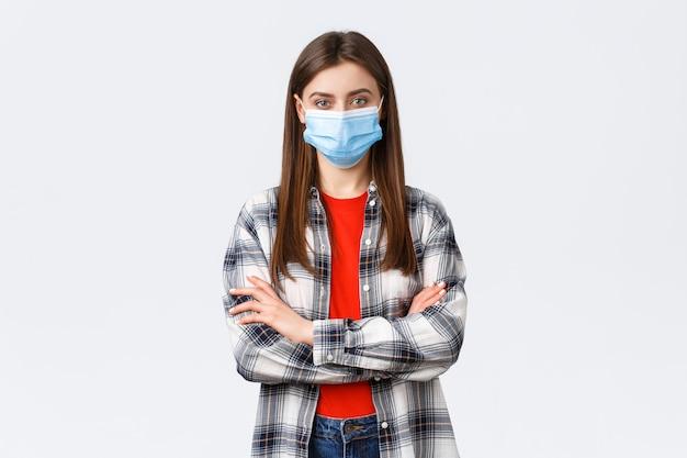 コロナウイルスの発生、検疫の余暇、社会的距離と感情の概念。チェックシャツを着た自信のある若い女性は、医療用マスク、クロスアームチェスト、決定的な外観のカメラを着用します。