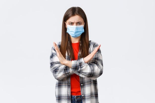 コロナウイルスの発生、検疫の余暇、社会的距離と感情の概念。十分、これは停止する必要があります。医療マスクの抗議で深刻な不機嫌な若い女性、クロスサインを表示します。