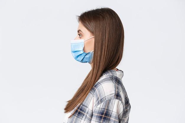 코로나바이러스 발병, 격리 여가, 사회적 거리 및 감정 개념. 흰색 배경에 서 있는 의료 마스크를 쓴 진지해 보이는 젊은 예쁜 여성의 프로필