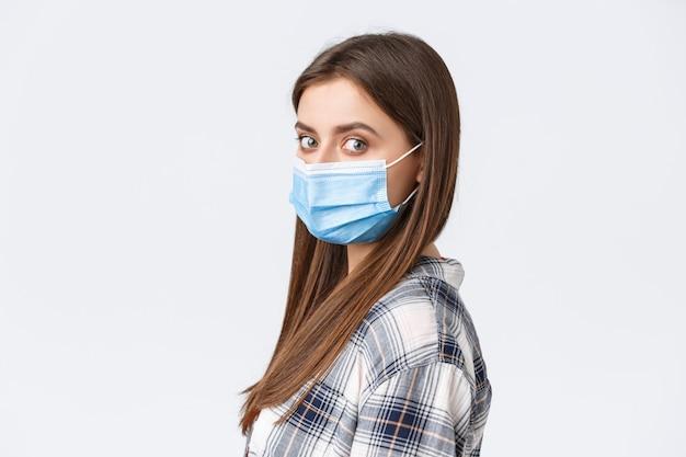 코로나바이러스 발병, 격리 여가, 사회적 거리 및 감정 개념. 진지한 젊은 매력적인 여성의 프로필 사진, 의료 마스크를 쓴 학생이 얼굴 카메라를 돌립니다.