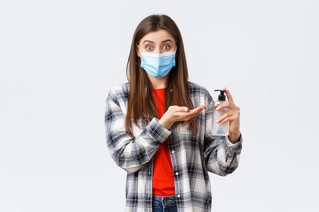 コロナウイルスの発生、検疫の余暇、社会的距離と感情の概念。ウイルスのキャッチを防ぐ笑顔の女の子、医療マスクを着用し、手指消毒剤、白い背景を適用します。