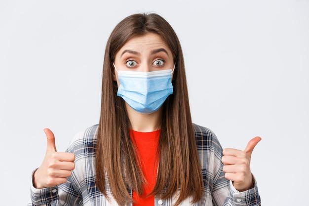 코로나바이러스 발병, 격리 여가, 사회적 거리 및 감정 개념. 잘 들린다. 의료용 마스크를 쓴 흥분되고 만족스러운 여성, 엄지손가락을 치켜드는 재미있는 아이디어를 보여줍니다.
