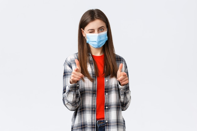 コロナウイルスの発生、検疫の余暇、社会的距離と感情の概念。あなたはそれを点在させることができます。カメラを指して、ウィンクしておめでとう、医療マスクの支持的な若い魅力的な女性。