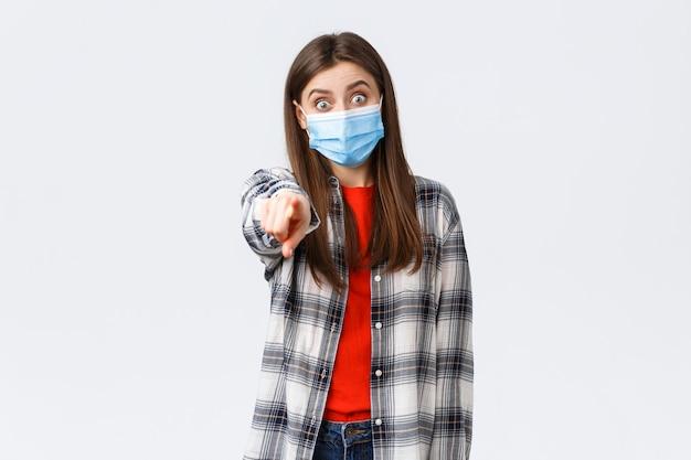 Focolaio di coronavirus, tempo libero in quarantena, distanza sociale e concetto di emozioni. la ragazza stupita e impressionata, eccitata riconosce qualcuno, punta la fotocamera con il dito, indossa una maschera medica