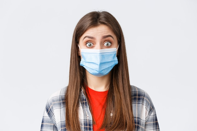 Focolaio di coronavirus, tempo libero in quarantena, distanza sociale e concetto di emozioni. primo piano di una donna incuriosita e sorpresa ascolta notizie interessanti, indossa una maschera medica, allarga gli occhi
