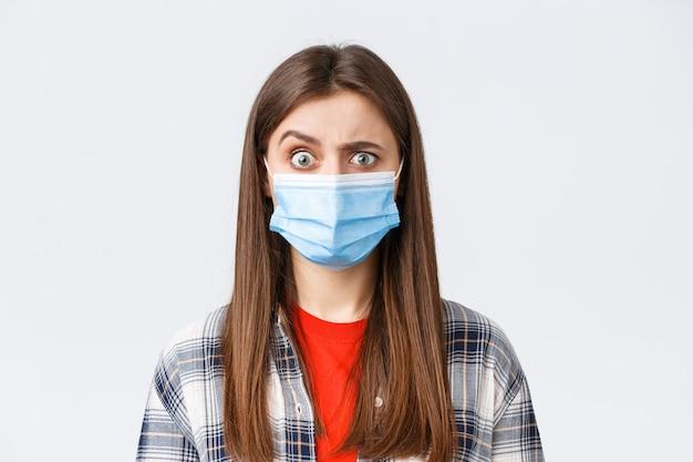 Focolaio di coronavirus, tempo libero in quarantena, distanza sociale e concetto di emozioni. ragazza confusa e spaventata in maschera medica che vede qualcosa di strano, alza il sopracciglio scettico.