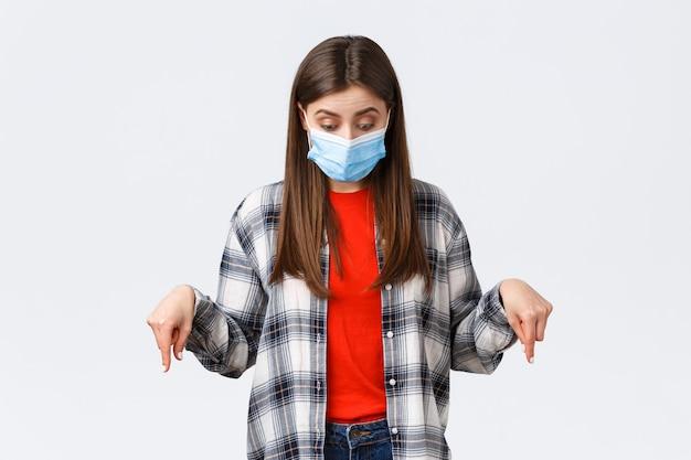 Focolaio di coronavirus, tempo libero in quarantena, distanza sociale e concetto di emozioni. ragazza carina incuriosita in maschera medica. donna che indossa i dpi a causa di un'infezione da virus, con lo sguardo rivolto verso il basso