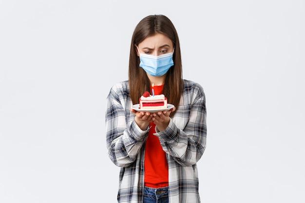 コロナウイルスの発生、社会的距離と休日のお祝いの概念の間のライフスタイル。誕生日ケーキの火のともったろうそく、思考、白い背景で困惑して見つめている医療マスクの混乱した女性。
