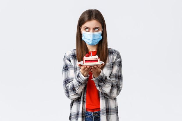 コロナウイルスの発生、社会的距離と休日のお祝いの概念の間のライフスタイル。医療用マスクの真面目な誕生日の女の子、火のともったろうそくでb-dayケーキを保持することを考えて、願い事をすることに焦点を当てます。