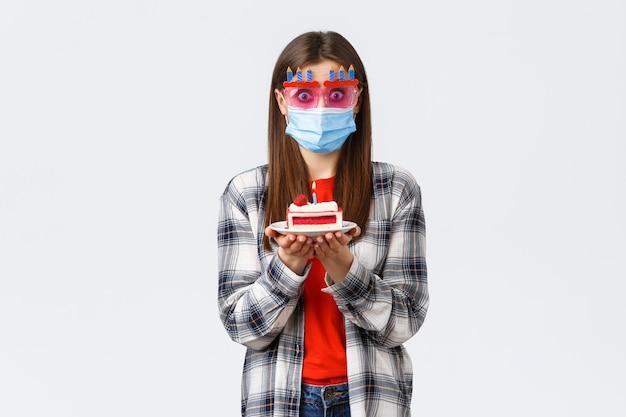 코로나바이러스 발병, 사회적 거리두기 기간 동안의 생활 방식 및 휴일 축하 개념. 안경과 의료용 마스크를 쓴 귀여운 소녀가 놀라거나 매복을 입고 생일 케이크를 들고 촛불을 부는 방법을 혼란스러워했습니다.
