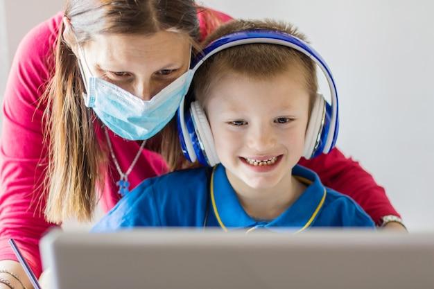 코로나 바이러스 발생. 폐쇄 및 학교 폐쇄. 집에서 온라인 수업을 공부하는 그의 sonwith 얼굴 마스크를 돕는 어머니.