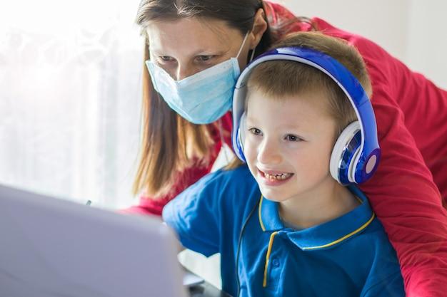 コロナウイルスアウトブレイク。ロックダウンと学校の閉鎖。母親が息子とフェイスマスクを手伝って、自宅でオンラインクラスを勉強しています。