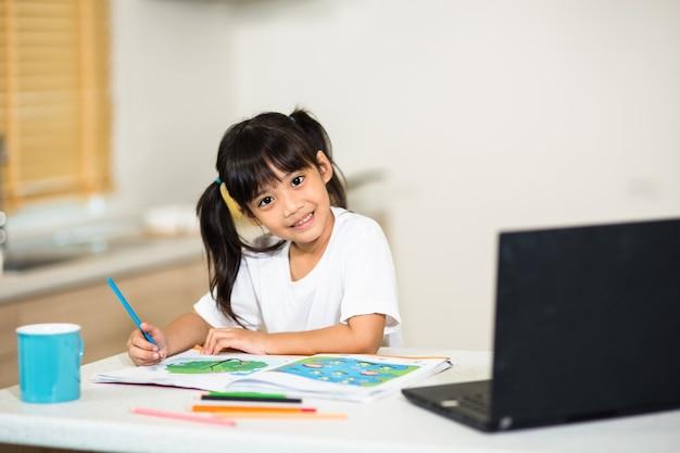 코로나 바이러스 발생. 폐쇄 및 학교 폐쇄. 온라인 교육 수업을 보고 있는 여학생, 집에서 인터넷으로 선생님과 행복한 이야기를 나누는 여학생. covid-19 전염병은 아이들에게 온라인 학습을 강요합니다