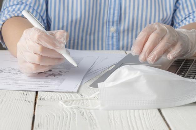 コロナウイルスアウトブレイク。自宅で作業し、ウイルスや細菌から保護するための外科用使い捨て手袋を着用する男性