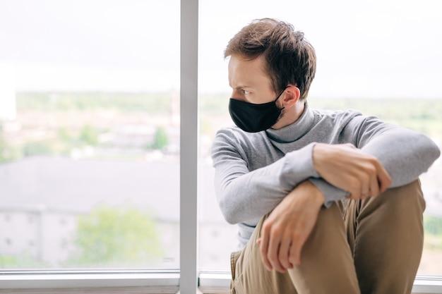 코로나 바이러스 발생 상황. 자가 격리 감염된 남자는 집 창문을 통해 거리를 바라보고있다. 프리미엄 사진