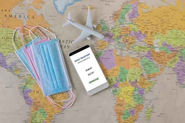 コロナウイルスの発生状況、パンデミック後の免疫パスポートでの旅行、リスクのない証明書携帯電話メモcovid-19コロナウイルス、パスポート、世界地図上の医療用マスク