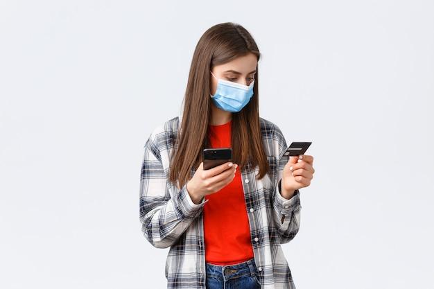 Focolaio di coronavirus, lavoro da casa, shopping online e concetto di pagamento senza contatto. la ragazza in maschera medica paga l'ordine di generi alimentari dal negozio di alimentari per consegnare, tenere il telefono cellulare e la carta di credito.