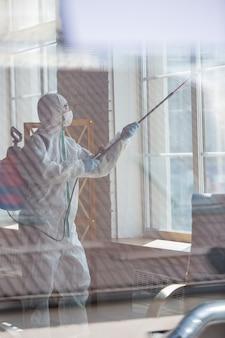 コロナウイルスパンデミック。防護服とマスクの消毒剤が部屋に消毒剤をスプレーします。