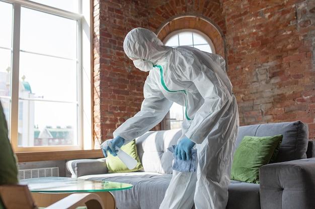 コロナウイルスパンデミック防護服とマスクを着用した消毒器が警告サインを作成