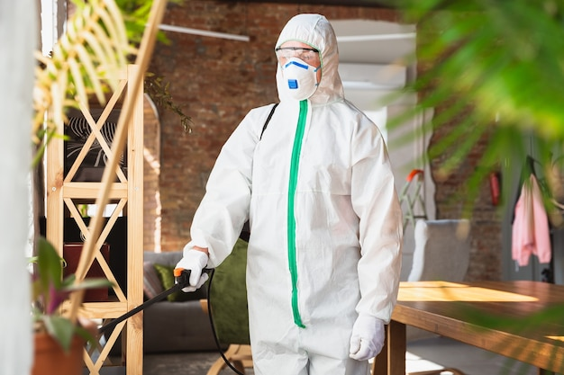 코로나 바이러스 감염병 세계적 유행. 보호복과 마스크를 쓴 소독제는 집이나 사무실에 소독제를 뿌립니다. covid-19 질병에 대한 보호. 표면으로 폐렴 바이러스 확산 방지.