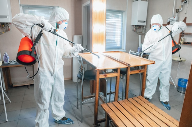 Коронавирус пандемия. дезинфектор в защитном костюме и маске распыляет дезинфицирующие средства дома или в офисе. защита от заболевания covid-19. профилактика распространения вируса пневмонии с поверхностей.