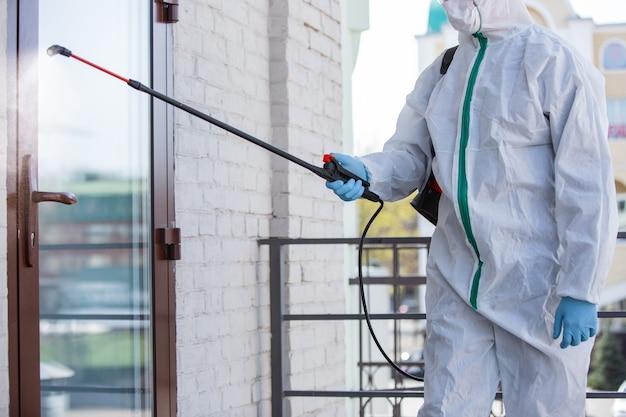 コロナウイルスパンデミック。防護服とマスクを着用した消毒剤は、家やオフィスに消毒剤をスプレーします。 covid-19病に対する防御。表面拡大肺炎ウイルスの予防。