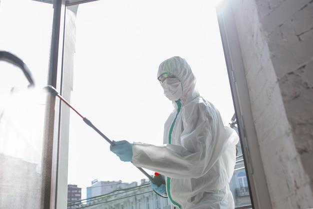 Коронавирус пандемия. дезинфектор в защитном костюме и маске распыляет дезинфицирующие средства дома или в офисе. защита от болезни covid-19. профилактика распространения вируса пневмонии с поверхностей.