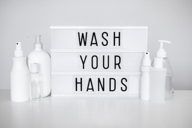 コロナウイルスのパンデミックと手指衛生の概念-手を洗うメッセージと白い上に消毒剤または液体石鹸のさまざまなボトルが付いたライトボックス