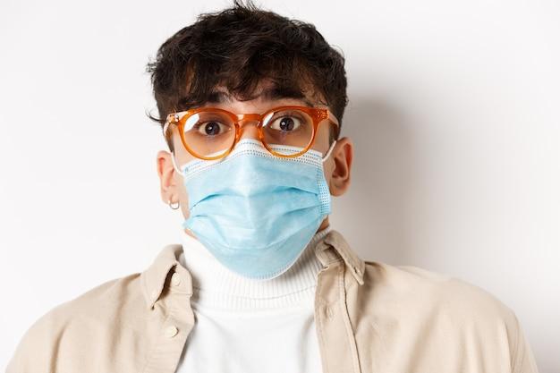 Концепция пандемии коронавируса и здоровых людей. удивленный парень в очках и маске, поднимая брови, с трепетом смотрит, стоя на белой стене.