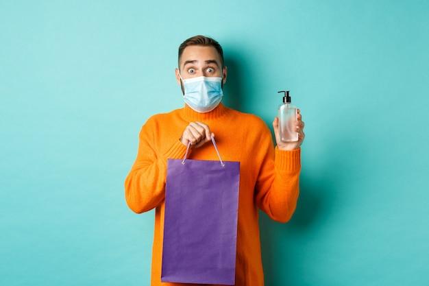 코로나 바이러스, 유행병 및 라이프 스타일 개념. 쇼핑백과 손 소독제를 보여주는 얼굴 마스크 맨