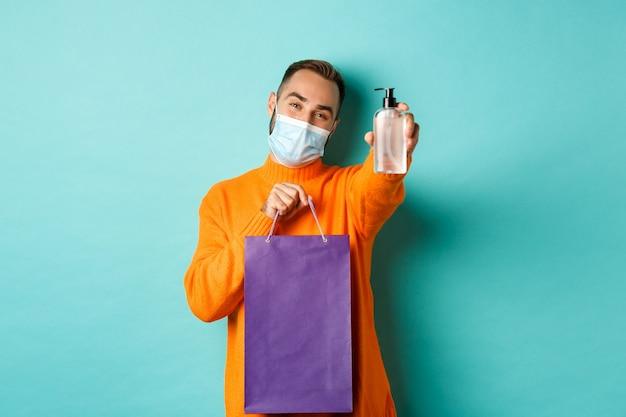 コロナウイルス、パンデミック、ライフスタイルの概念。ショッピングバッグと手を示すフェイスマスクの男