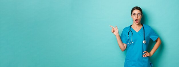 코로나바이러스, 전염병 및 사회적 거리 개념. 놀라워 보이는 아름다운 여성 의사의 클로즈업, 복사 공간에 손가락을 왼쪽으로 가리키고 파란색 배경 위에 서 있는
