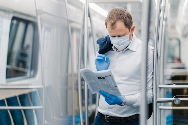 Coronavirus pandemic, covid-19, quarantine measure. serious adult man in white shirt, holds black jacket, concentrated in newspaper, wears protective mask and gloves, poses at metro carriage