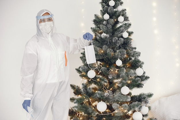 コロナウイルスパンデミックコビッド-2019。防護服、グーグル、手袋、マスク。クリスマスツリーは医療用マスクで飾られています。